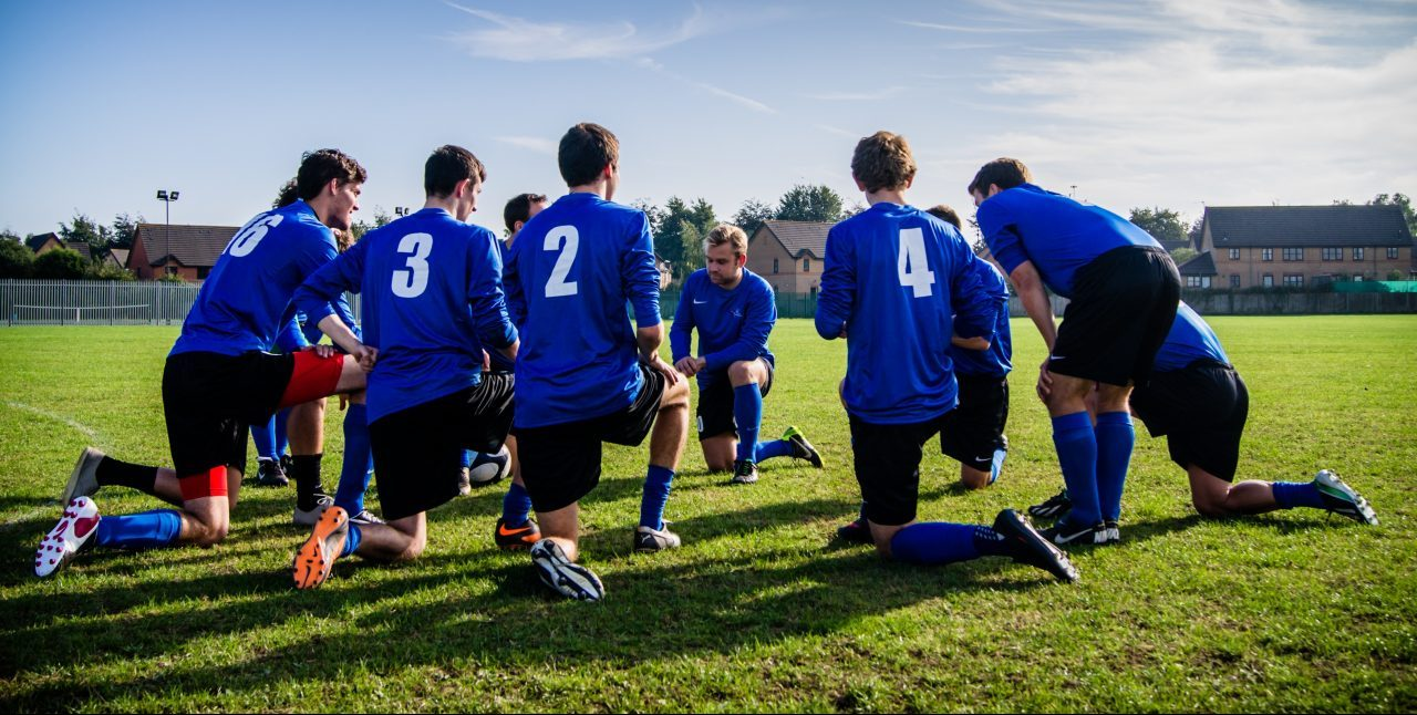 soccer team kneeling in huddle